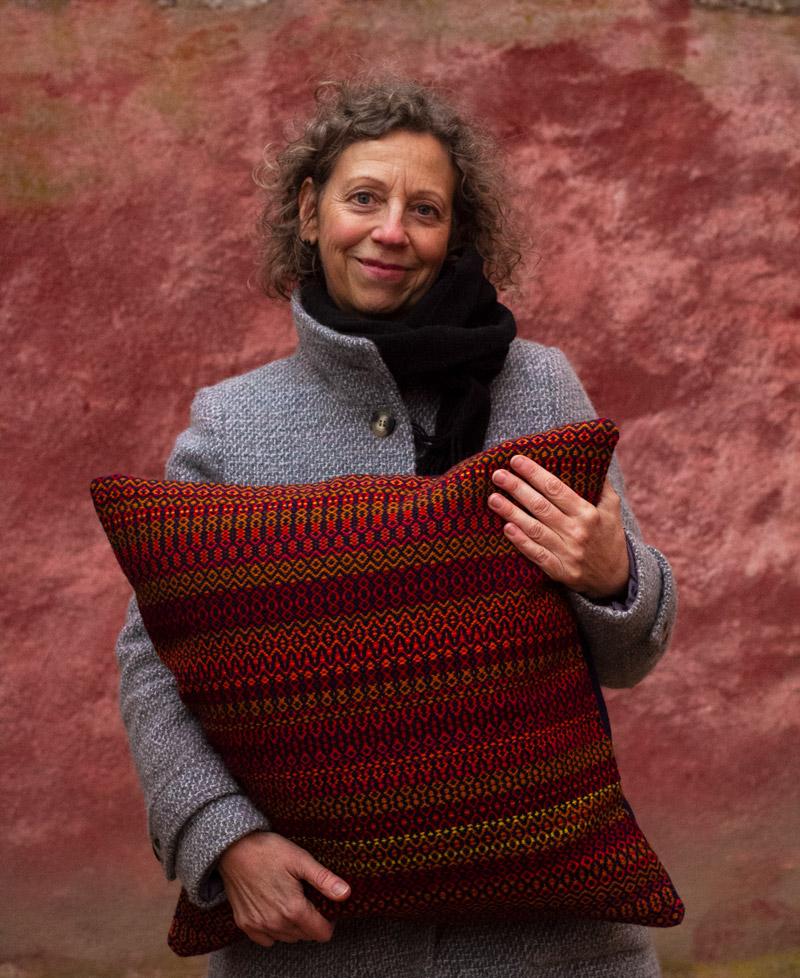 Bettina Posselt står mot en röd vägg och kramar om en kudde
